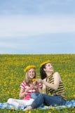 Mutter und Tochter, die auf Löwenzahnfeld sitzen stockfotos