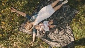 Mutter und Tochter, die auf Rasen liegen Glück der Mutterschaft und der Kindheit stock footage
