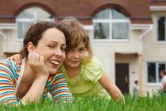 Mutter und Tochter, die auf Rasen vor Haus liegen stockfotos