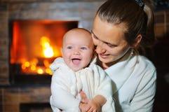 Mutter und Tochter, die auf Sofa By Cosy Log Fire sich entspannen Stockfotos