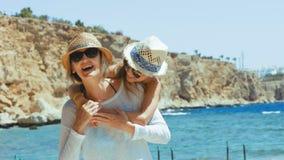Mutter und Tochter, die auf Strand umarmen stock video footage