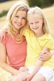 Mutter und Tochter, die auf Stroh-Ballen in Harv sitzen Lizenzfreies Stockbild