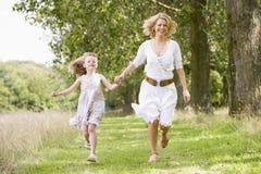 Mutter und Tochter, die auf Waldpfad laufen Stockbilder