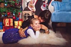 Mutter und Tochter, die auf weißem Pelz mit Geschenken liegen Stockfoto