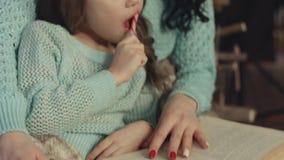 Mutter und Tochter, die das Buch nahe dem hölzernen Weihnachtsbaum lesen stock video footage