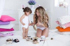Mutter und Tochter, die das Make-up sitzt auf dem Bett im Schlafzimmer tut Stockfotografie