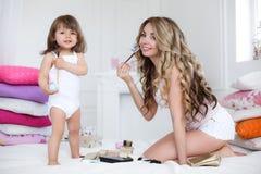 Mutter und Tochter, die das Make-up sitzt auf dem Bett im Schlafzimmer tut Lizenzfreie Stockfotos