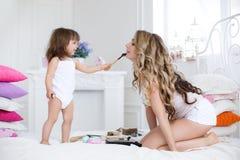 Mutter und Tochter, die das Make-up sitzt auf dem Bett im Schlafzimmer tut Lizenzfreie Stockbilder