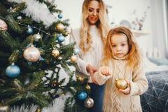 Mutter und Tochter, die den Baum verzieren Stockbilder
