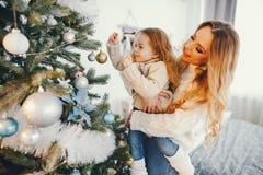 Mutter und Tochter, die den Baum verzieren Stockfotografie