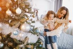 Mutter und Tochter, die den Baum verzieren Lizenzfreies Stockbild