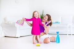 Mutter und Tochter, die den Boden fegen Stockfotos