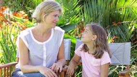 Mutter und Tochter, die in den Garten-Stühlen und der Unterhaltung sitzen stock footage
