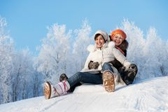 Mutter und Tochter, die in den Schnee schieben stockfoto