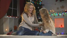 Mutter und Tochter, die den Spaß, nahe Weihnachtsbaum kitzelnd, Feiertage hat stock footage