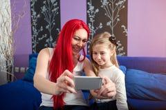 Mutter und Tochter, die den Spaß nimmt selfie hat Stockbild