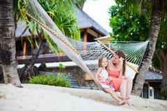 Mutter und Tochter, die in der Hängematte sich entspannen Stockbilder