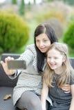 Mutter und Tochter, die in der Natur und in Unterhaltungsselfie sitzen Stockfoto