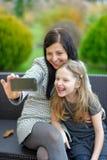Mutter und Tochter, die in der Natur und in Unterhaltungsselfie sitzen Stockfotos
