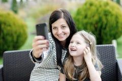 Mutter und Tochter, die in der Natur und in Unterhaltungsselfie sitzen Lizenzfreies Stockfoto