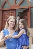 Mutter und Tochter, die die Schlüssel zu ihrem neuen Haus lächeln und halten stockfoto