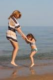 Mutter und Tochter, die in die Wellen springen Stockfoto