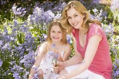 Mutter und Tochter, die draußen Blumen anhalten Lizenzfreies Stockbild