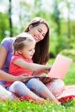Mutter und Tochter, die draußen Laptop verwendet Lizenzfreie Stockfotos