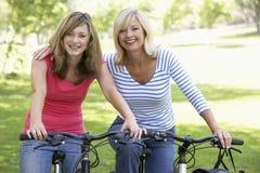 Mutter und Tochter, die durch einen Park einen Kreislauf durchmachen lizenzfreies stockbild