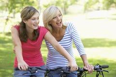 Mutter und Tochter, die durch einen Park einen Kreislauf durchmachen Lizenzfreie Stockfotos