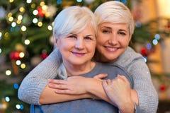 Mutter und Tochter, die durch Weihnachtsbaum umarmen lizenzfreies stockfoto