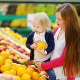 Mutter und Tochter, die eine Orange in einem Speicher wählen Lizenzfreie Stockbilder