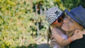 Mutter und Tochter, die in einem Park an einem Sommertag küssen und sich umarmen stock footage