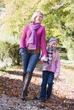 Mutter und Tochter, die entlang Waldpfad gehen lizenzfreie stockbilder