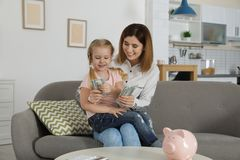 Mutter und Tochter, die Geld auf Sofa z?hlen lizenzfreies stockbild