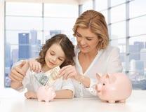 Mutter und Tochter, die Geld zu den Sparschweinen stecken Lizenzfreies Stockfoto