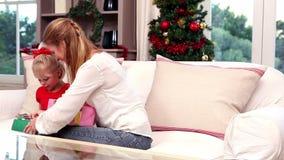 Mutter und Tochter, die Geschenke am Weihnachten austauschen stock footage