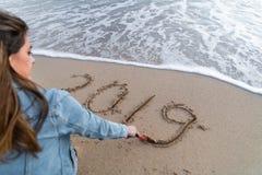 Mutter und Tochter, die 2019 geschrieben auf den Sand betrachtet lizenzfreies stockfoto