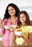 Mutter und Tochter, die Getreide und Frucht essen Lizenzfreie Stockfotos