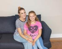 Mutter und Tochter, die glücklich auf einer Couch in Seattle, Washington aufwerfen stockfoto
