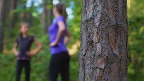 Mutter und Tochter, die Gymnastik im Wald tun stock footage