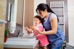 Mutter und Tochter, die ihre Hände im Badezimmer waschen Interessieren Sie sich Stockfoto