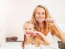 Mutter und Tochter, die ihre Z?hne putzen lizenzfreies stockbild