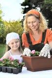 Mutter und Tochter, die im Garten arbeitenzeit haben Stockfotos