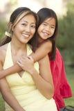 Mutter und Tochter, die im Garten umarmen Stockfoto