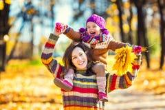 Mutter und Tochter, die im Herbstpark spielen Stockfotos