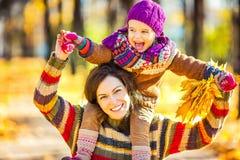 Mutter und Tochter, die im Herbstpark spielen Stockbilder