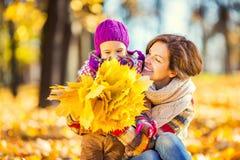 Mutter und Tochter, die im Herbstpark spielen lizenzfreies stockbild