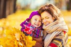 Mutter und Tochter, die im Herbstpark spielen lizenzfreies stockfoto