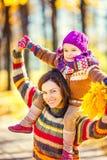 Mutter und Tochter, die im Herbstpark spielen Lizenzfreie Stockfotos